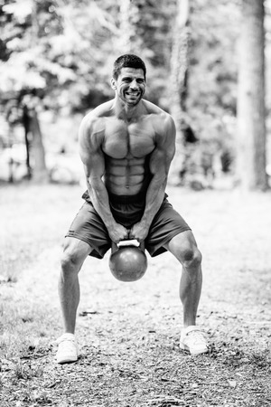 kettle bell: Crossfit athlete training outdoors with kettle bell weight. Black and white