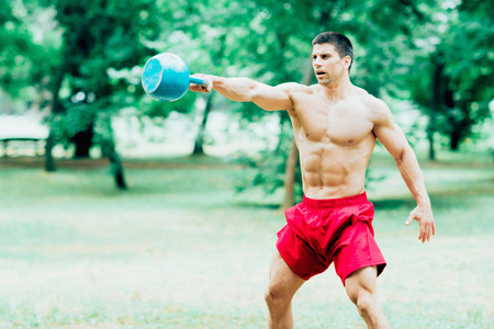 kettle bell: Muscular young man exercising with kettle bell