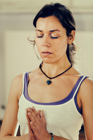 meditation room: Woman meditating with hands in prayer position. Toned image