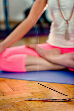 ashtanga: Woman meditating on a hardwood floor. Focus on incense stick and smoke, unrecognizable yoga practitioner blurred in the back