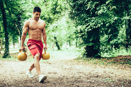 lunges: Muscular athlete male walking with kettle bells, doing lunges