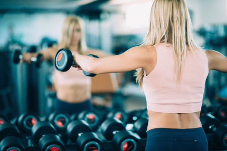 mirror image: Attractive young woman exercising with weights in the gym. Looking in the mirror, satisfied with her progress. Toned image
