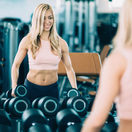 mirror image: Attractive female athlete exercising with weights in the gym. Smiling, working out in front of the mirror. Toned image, focus set on mirror