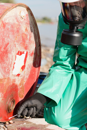 environmentalist: Environmentalist in protective suit taking sample of leaking fluid from discarded barrel Stock Photo