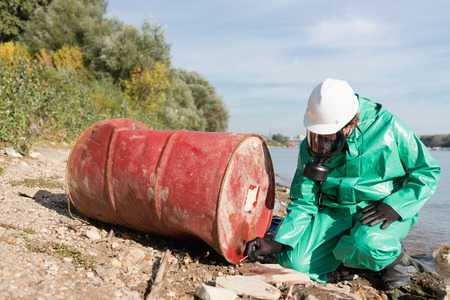 damage control: Pollution control official working examining contents of discarded barrel