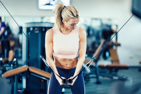 crossover: Attractive girl working out on cable crossover exercising machine