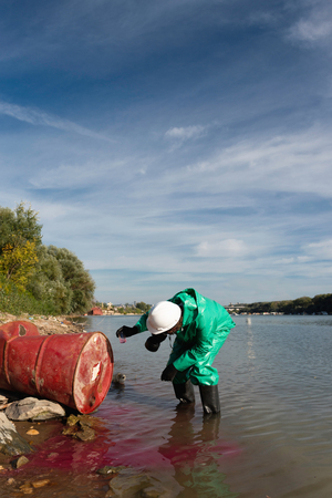 environmentalist: Environmentalist in protective suit taking sample of toxic substance leaking from drum Stock Photo