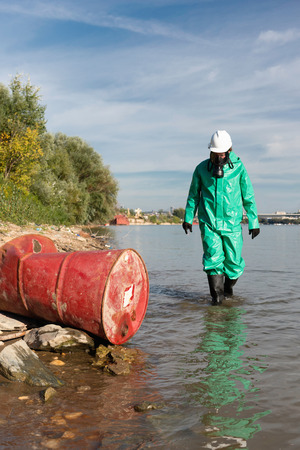hazardous waste: Pollution control official approaching barrel with hazardous waste