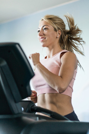 toned image: Attractive young woman jogging on treadmill. Selective focus, toned image