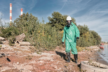 damage control: Environmentalist in protective suit working at a pollution site. Contamination of air, water and soil. Pollution factors like factory chimneys, old tires, plastic bottles, chemicals and other waste, all represented in the photo. Stock Photo