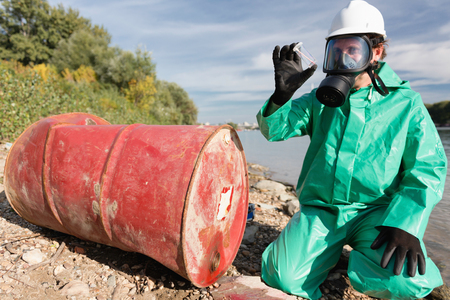 damage control: Pollution control official looking at sample of leaked chemicals collected by the river Stock Photo