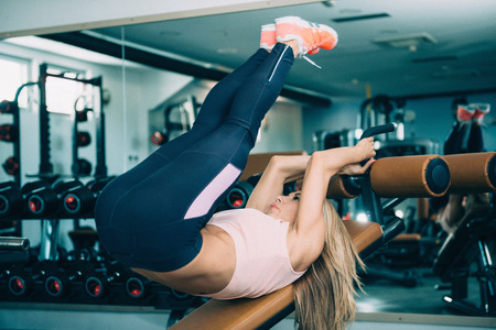 abdominal muscles: Attractive young woman exercising on adjustable decline bench, addressing abdominal muscles