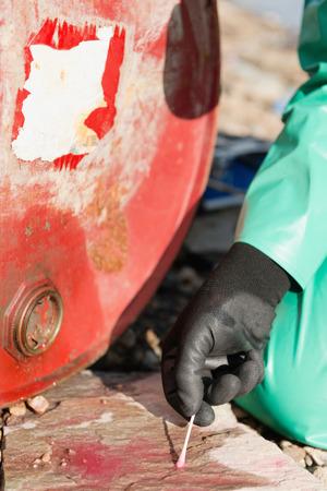 environmentalist: Environmentalist taking sample of chemical leaked from steel drum