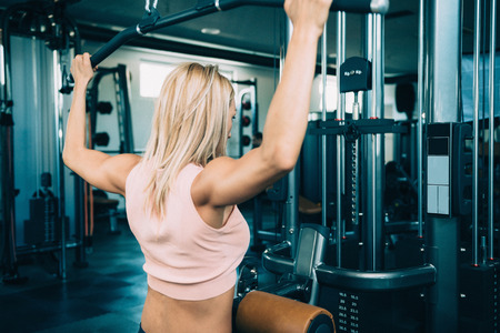 lats: Woman doing lats pull-down workout in the gym