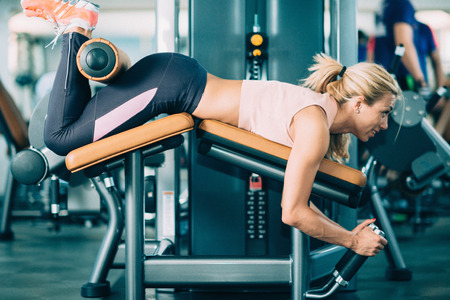 横になっている脚カール マシンでジムで運動する女性アスリート 写真素材