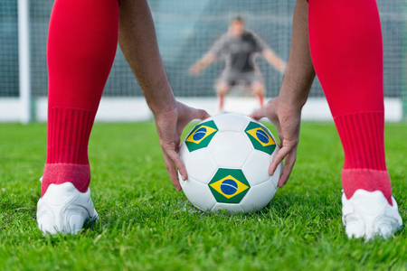 uniform green shoe: Penalty shootout - striker placing Brazilian ball on a penalty spot