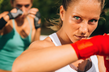 two persons only: Hook punch - woman on tae bo training Stock Photo