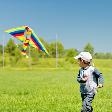 only 3 people: Little boy playing with kite Stock Photo