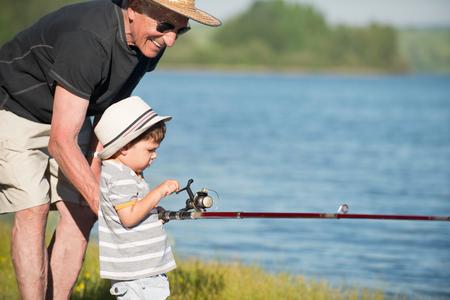 Active senior fishing with grandson 版權商用圖片