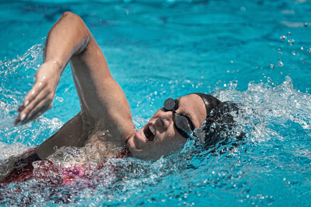 action shot: Front crawl swimmer. High speed action shot, focus set on face Stock Photo