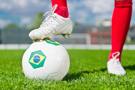 uniform green shoe: Soccer player standing on Brazilian soccer ball Stock Photo