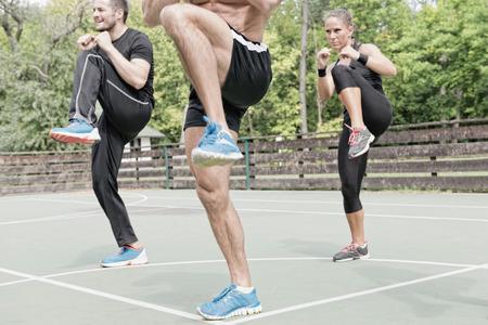 Three people on tae bo training, focus on legs