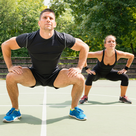 cardiovascular workout: Insanity workout trainer doing squats with female athlete
