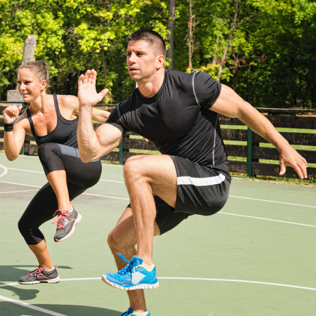 cardiovascular workout: Two athletes doing knee up exercises