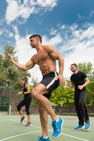 cardiovascular workout: Fitness instructor with stopwatch, cardio training outdoors Stock Photo