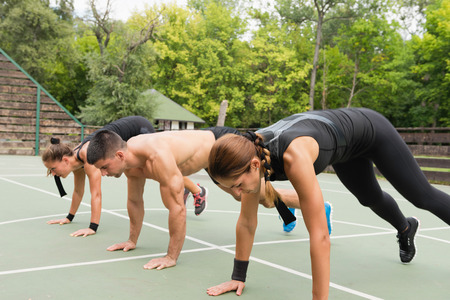 cardiovascular workout: Group of people exercising outdoors