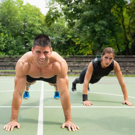 cardiovascular workout: Male and female athletes doing push-ups Stock Photo