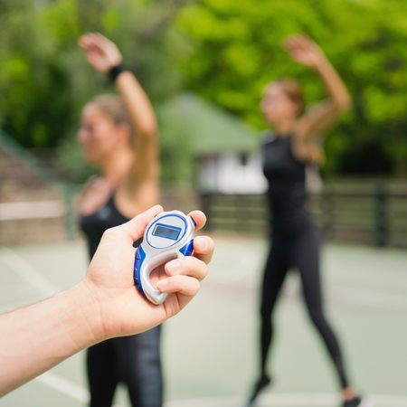 cardiovascular workout: Trainer with stopwatch during outdoor exercise class