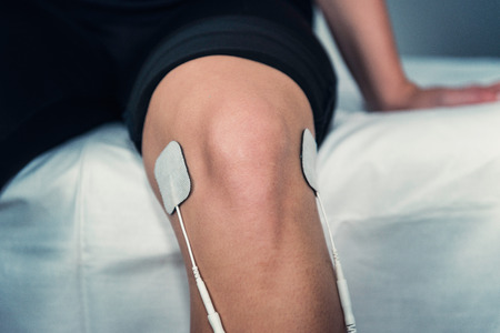 TENS treatment in physical therapy - electrodes placed onto patient's knee