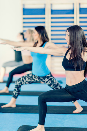 four person only: Women in Warrior II pose on yoga class