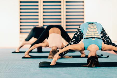 power yoga: Power Yoga - group of women on power yoga class, prasarita padottanasana position