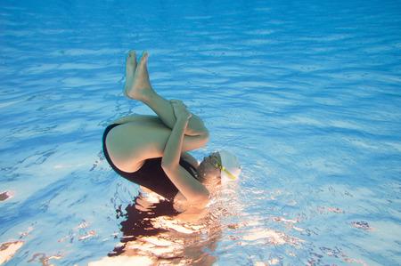 cabeza abajo: Acurrucado cuerpo de la mujer joven atractiva contra la superficie del agua. boca abajo debajo del agua.