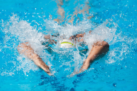 one person only: Butterfly stroke swimmer makes a splash. Frozen moment, no motion blur