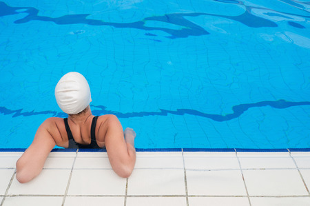 ''wide angle'': Young woman hanging on the poolside. Wide angle, convenient copy space.