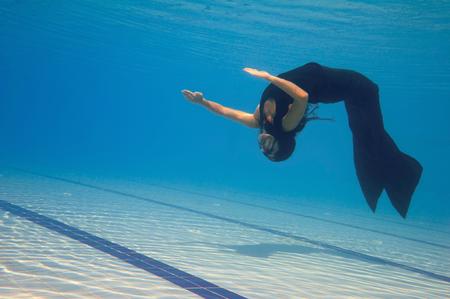 cabeza abajo: Sirena de natación boca abajo en la piscina. filtro polarizador, cómodo espacio de la copia