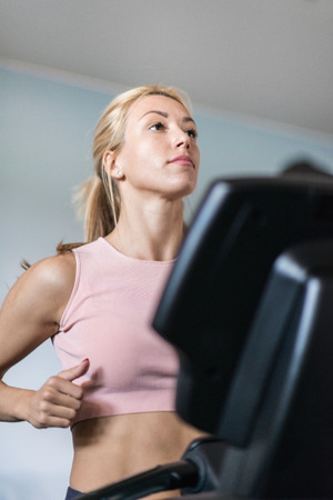 toned image: Attractive young woman running on treadmill. Selective focus, toned image