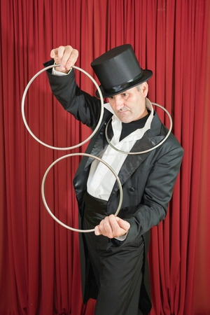 magic trick: Stage magician doing a classic magic trick with iron rings Stock Photo