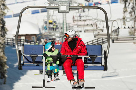 ski lift: Father and son on ski lift in winter vacation resort Stock Photo