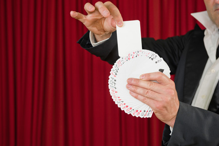 magic trick: Magic trick with playinMagician pulling a blank card out of deck.