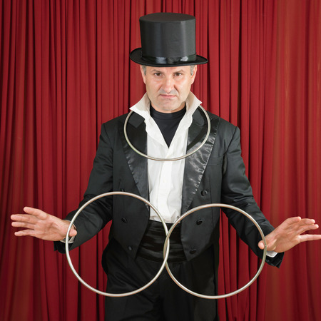 stage props: Magician with classic metal ring props, posing on stage
