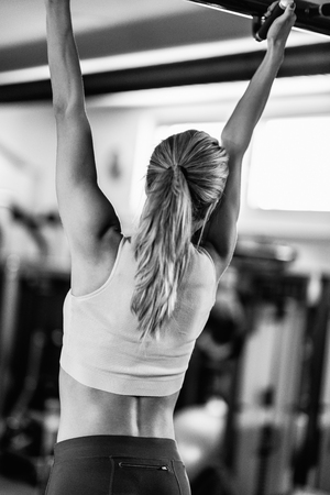 pullups: Female athlete doing pull-ups in the gym