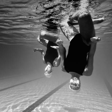duet: Synchronized swimming duet underwater Stock Photo
