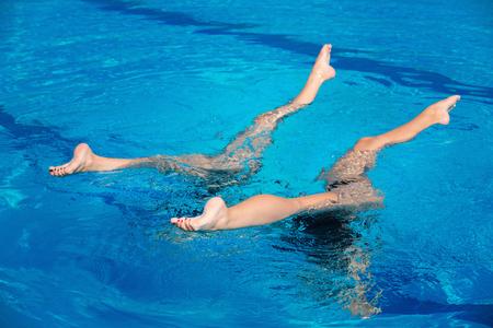 Synchroon zwemmen duet uitvoeren in zwembad