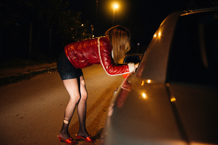 Street prostitute talking to car driver