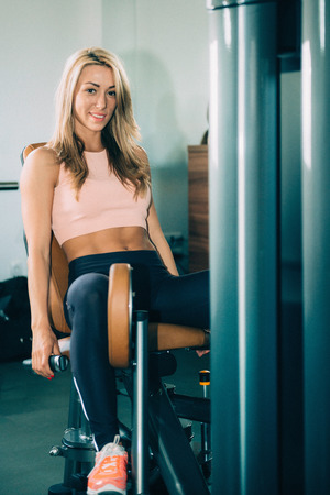 abductor: Abductor machine - Attractive girl exercising in the gym Stock Photo