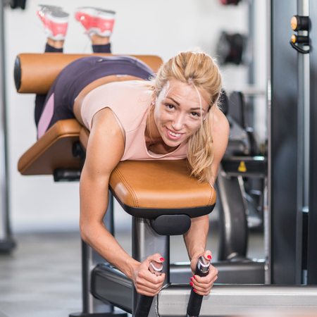 hamstrings: Female athlete exercising at lying leg curl bench in the gym Stock Photo